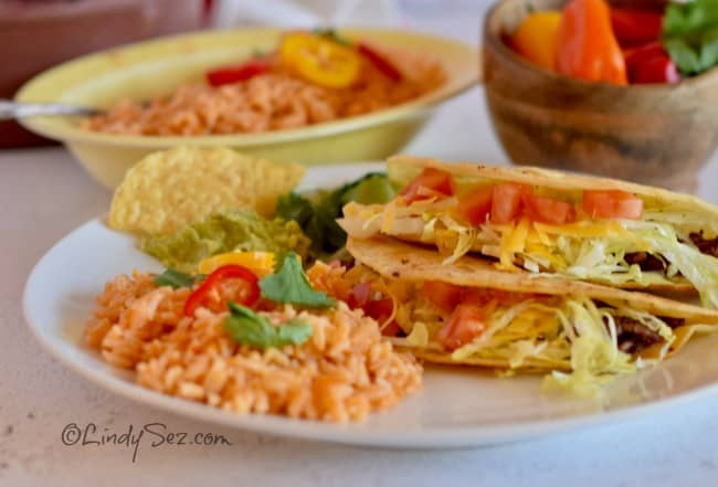 A plate with homemade tacos along side some Mexican Style Rice.