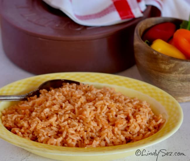 Authentic Mexican Style Rice in a dish with peppers and tortilla cooker in the background.