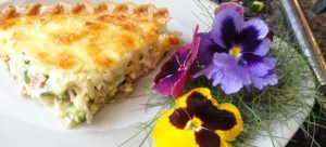 Bacon and Zucchini Quiche with beautiful poppies on a place.