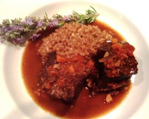 slow-braised beef short ribs with rosemary risotto in a bowl with rosemary sprig
