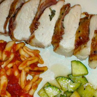 Crispy chicken breasts with sage and prosciutto on a white dish with pasta.
