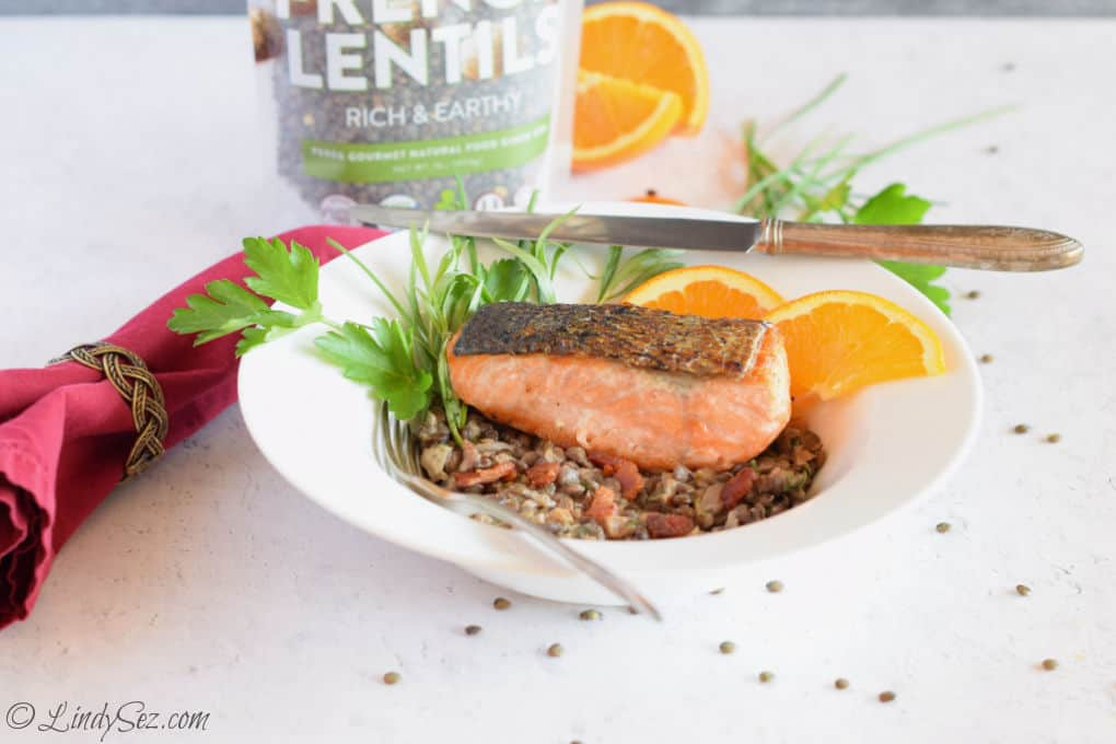 A bowl with lentils, bacon, and crispy skin salmon.