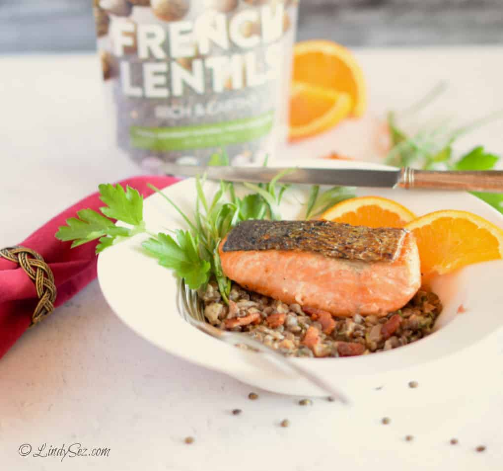 Crispy Skin Salmon with Lentils and Bacon in a white bowl with a bag of lentils behind it.