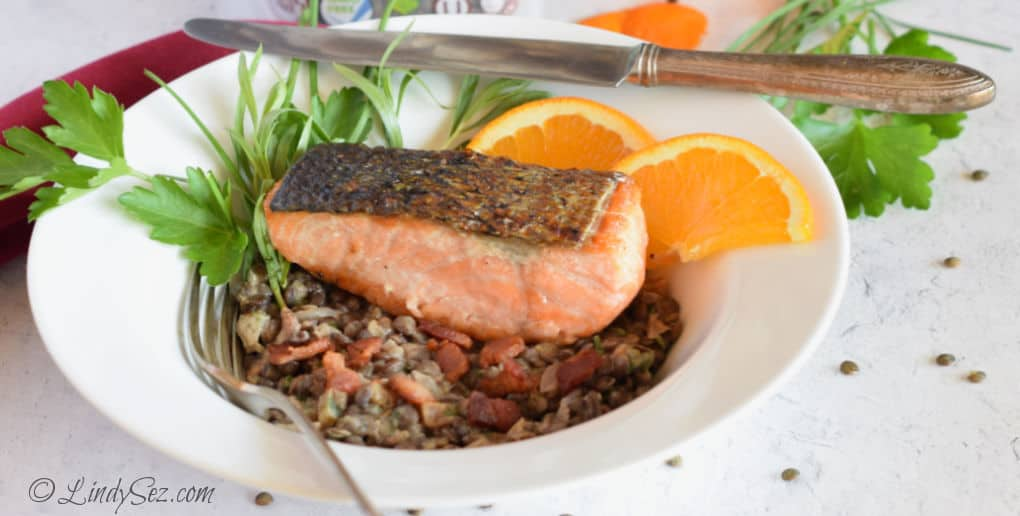 A plate with a more opaque piece of Crispy Skin Salmon.