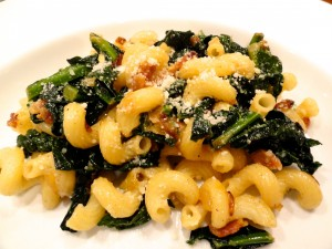 Pasta with kale, bacon and caramelized onions close up showing the curly noodles.