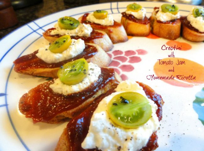 Crostini with Tomato Jam and Ricotta on a plate with colorful tomato toppings.