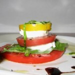 classic caprese salad on a plate with multi-colored tomatoes.