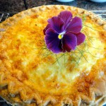 Quiche Lorraine with a purple pansy on top.