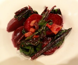 A terrible photo of warm beet salad with bacon and goat cheese ready to eat.