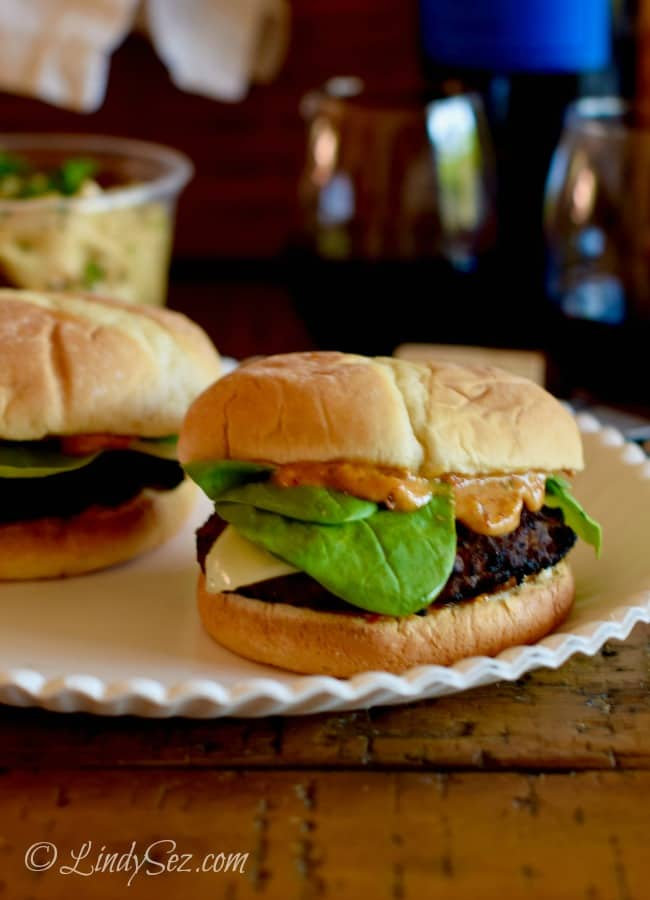 A shot of Caramelized Onion Bacon Burgers with a nice background of pasta salad.