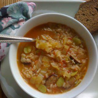 Smokey Kielbasa Cabbage soup in a bowl with a spoon.