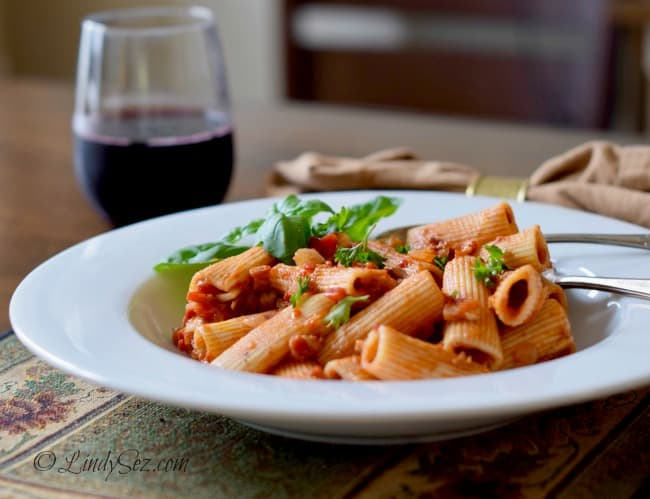 Rigatoni with Roasted Peppers, Tomatoes and Pancetta served with a glass of red wine