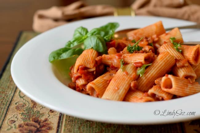 Rigatoni with Roasted Peppers, Tomatoes and Pancetta in a white bowl with basil leaves