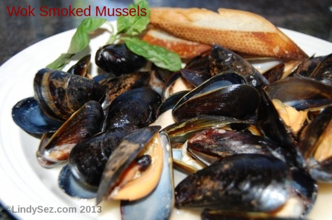 A bowl of wok smoked mussels with crostini.