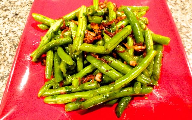 Green Beans with Toasted Walnuts and Prosciutto on a red plate