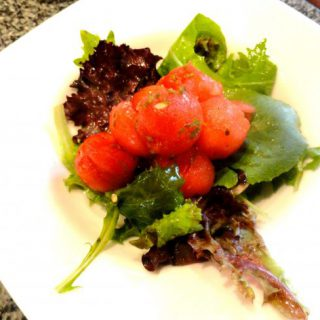 Minted Watermelon Salad on greens sitting on a white plate.