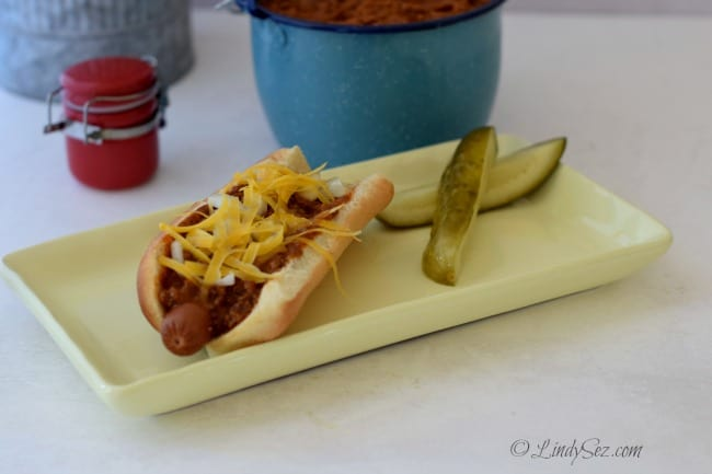 Lindy's Chili Gravy on a Chili Dog with pickles on a yellow plate.