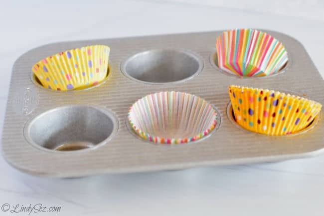 A muffin tin with colorful inserts is ready to bake some delicious muffins.