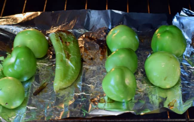 Roasting tomatillos on foil under the broiler.