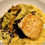 A plate showing a beautiful dish of Halibut and Forbidden Rice in a Saffron Cream Jus.