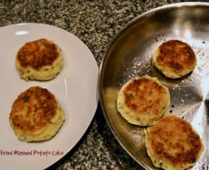 A skillet and a plate with some fried mashed potato cakes on them.