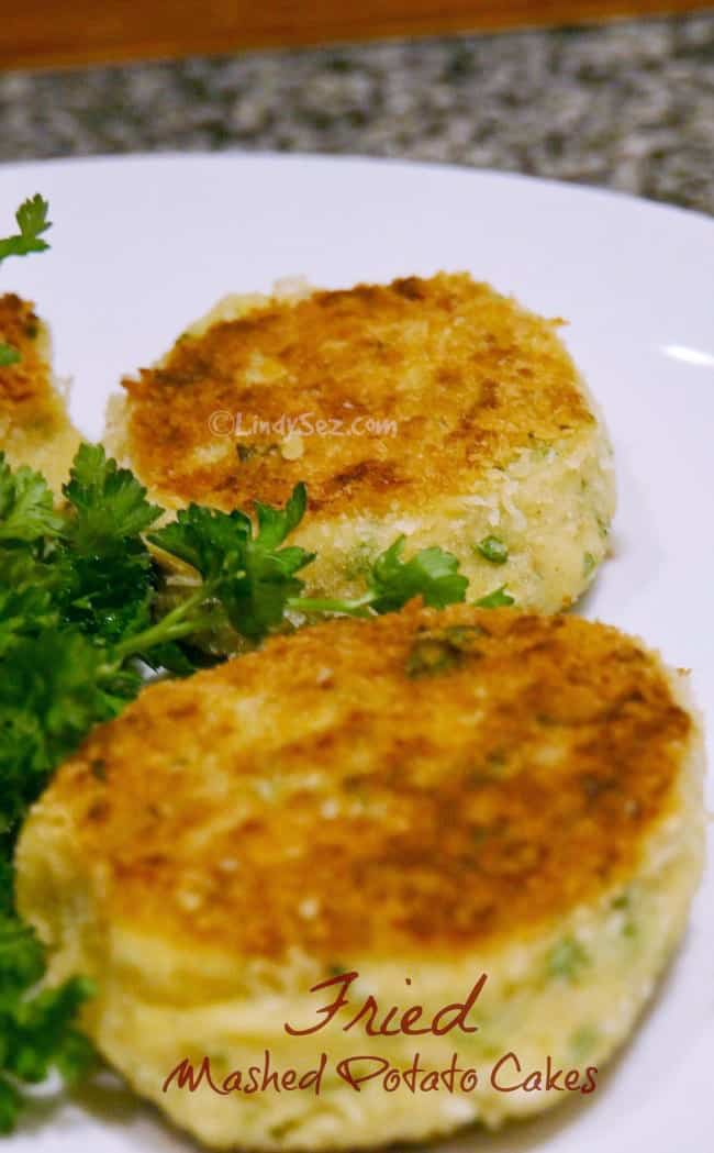 A plate with mashed potato cakes and garnish.