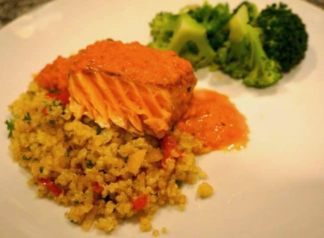 A plate with Quinoa, Salmon, Red Pepper Sauce, and broccoli.
