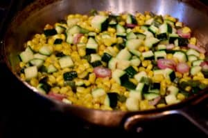 A bright and colorful pan with zucchini corn saute in it.