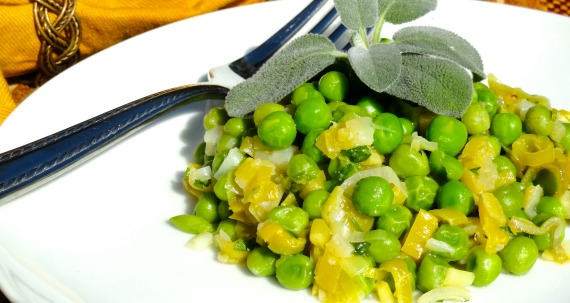 Braised Leeks and Fresh Peas on a plate with sage and a fork.