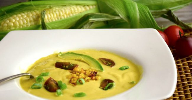 Roasted corn soup in a white bowl with a fresh ear of corn behind it.