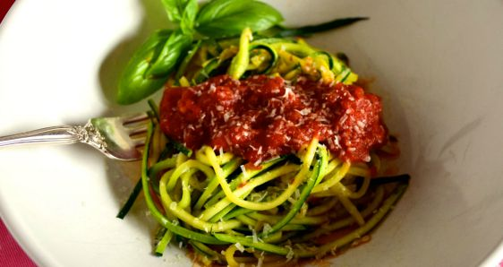 A close up of Zucchini spaghetti with Tomato sauce and fresh herbs.