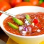 A chunky bowl of Gazpacho with fresh vegetables in the background.