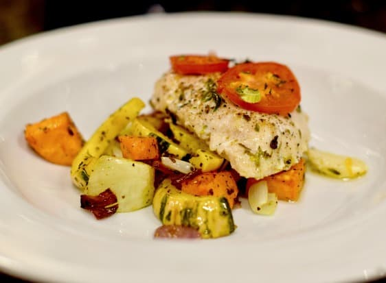 A plate of oven poached chicken with veggies