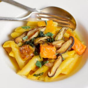 A white bowl with pasta, butternut squash, and shiitake mushrooms.