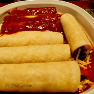 saucing a fully loaded cheese enchilada