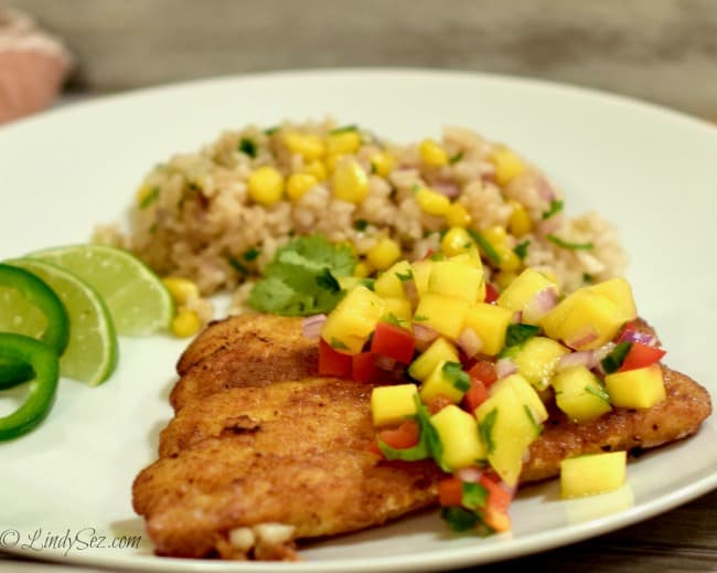 Simple Panfried Curry Snapper with Mango Salsa on a white plate with rice