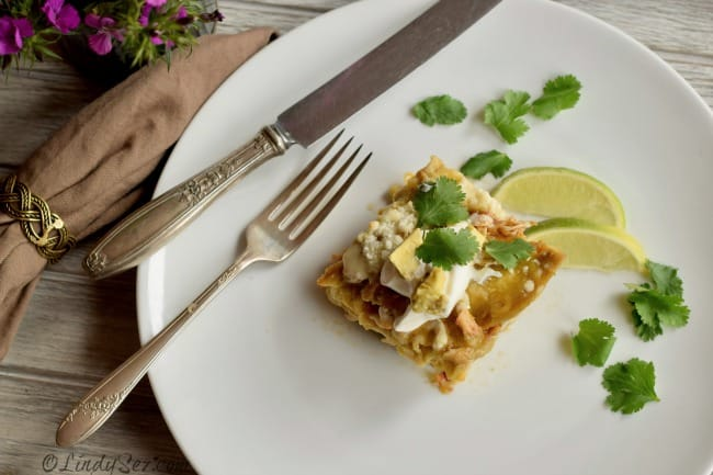 Sour cream and diced avocado adorn this serving of Green Chile Chicken Enchilada Stack