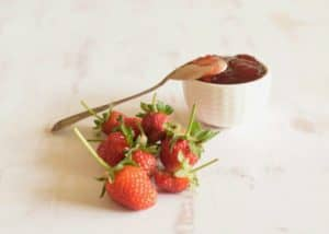 Easy Fresh Strawberry Jam with Balsamic header shot with white bowl and spoon.