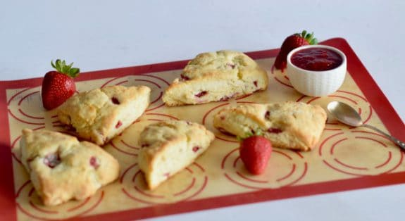 Freshly cooked strawberry cream scones with strawberries and jam