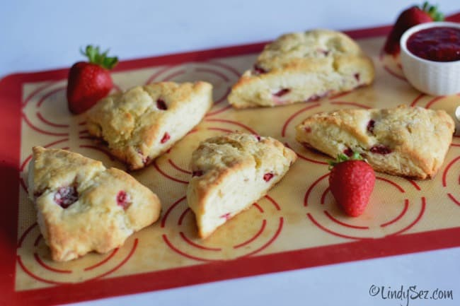 Baked and ready to eat fresh strawberry cream scones on a colorful baking sheet.