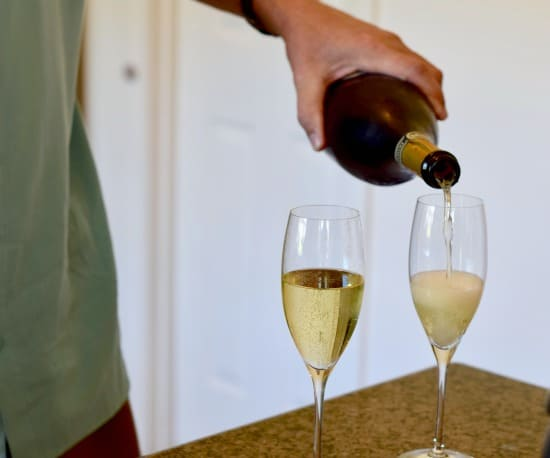 2 flutes being filled with sparkling wine.