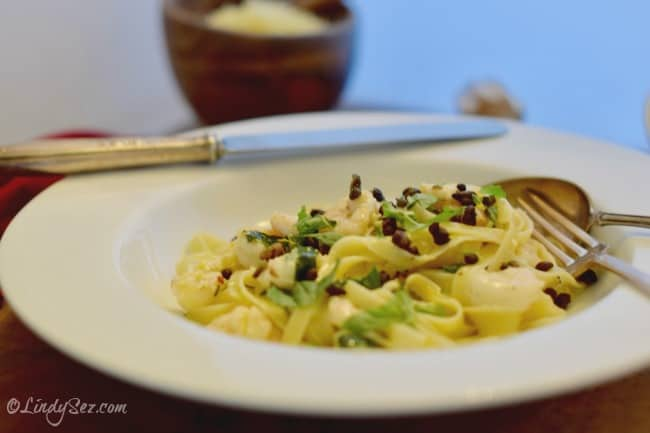 A bowl of Lemony Pasta ready to serve with some extra cheese in the background