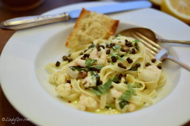 Lemony Pasta with Shrimp and Fried Capers in a bowl with garlic bread