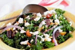 Massaged Kale Greek Salad in a yellow bowl
