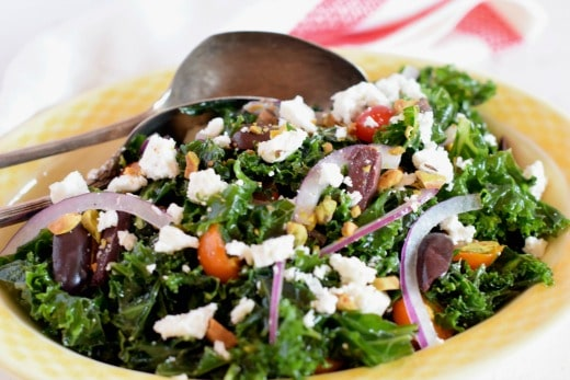 Massaged Kale Greek Salad in a yellow bowl