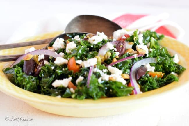 A side view of the massaged kale Greek salad with antique spoons