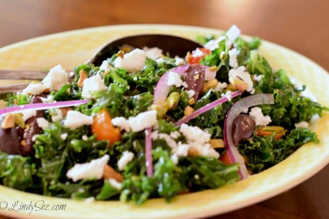 A yellow bowl with Massaged Kale Greek Salad ready to be served