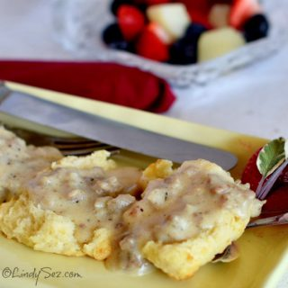 Simple Savory Sausage Gravy on a yellow plate with fresh fruit behind.