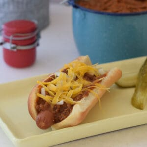 A hot dog dressed in chili sauce.
