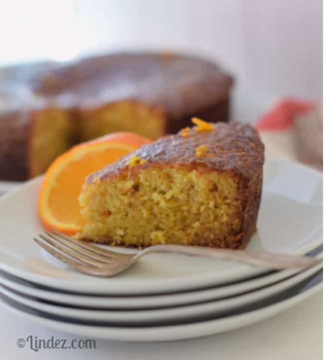 A slice of All In Whole Orange Cake on a plate with an orange.